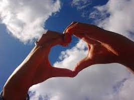 Hands in heart shape looking at clouds