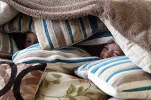 Child playing in pillow fort
