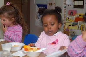 Child eating bowl of fruit salad