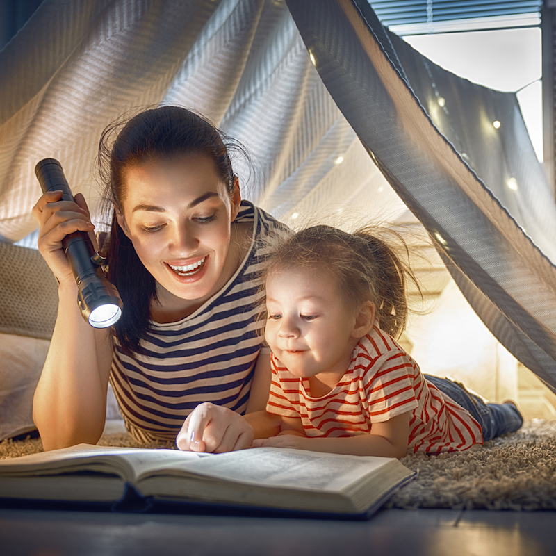 Mother and daughter reading book in tent